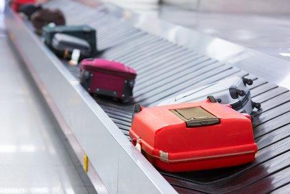Mehrere bunte Reisekoffer am Gepäckband
